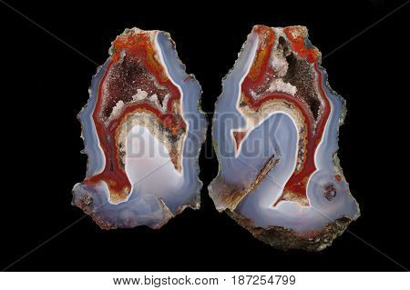 A cross section of the agate stone. At the top quartz geode with calcite bottom pseudomorph. Multicolored silica bands colored with metal oxides are visible. Origin: Asni Atlas Mountains Morocco.
