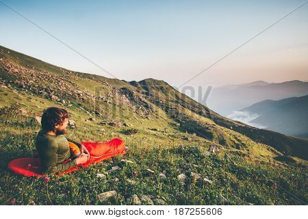 Man Traveler relaxing in sleeping bag camping enjoying sunset mountains landscape Travel Lifestyle hiking concept adventure summer vacations outdoor