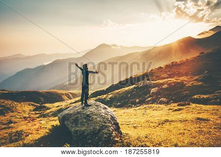 Man raised hands at sunset mountains Travel Lifestyle success and wellness emotional concept adventure vacations outdoor hiking harmony with nature aerial view