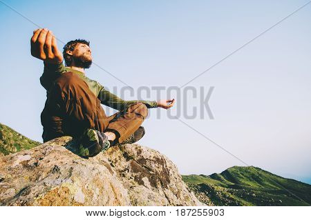 Man traveler meditating yoga at mountains Travel Lifestyle relaxation emotional concept adventure summer vacations outdoor harmony with nature