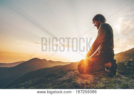 Man relaxing at sunset mountains Travel Lifestyle spiritual emotional meditating concept vacations outdoor harmony with nature landscape