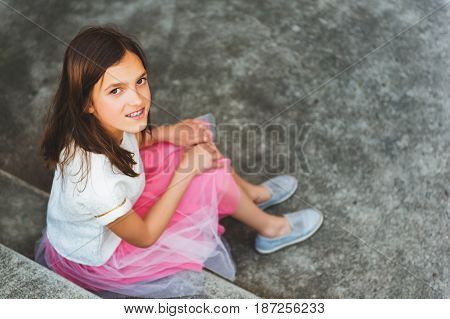 Preteen girl with teeth braces wearing beautiful dress, sitting on stairs, top view