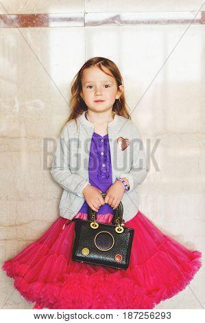 Sweet little toddler girl wearing fluffy tutu skirt, grey sweatshirt jacket, holding lady bag