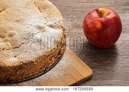 Apple pie with a red apple on a wooden table