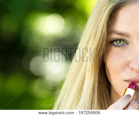 Beautiful young blonde woman corrects-applying red lipstick make-up in the park. Concept teenager lifestyle.