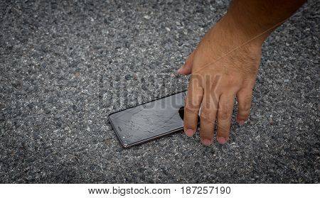 A Man Picking Smart Phone with broken screen on the Ground
