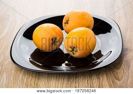 Black Plate With Ripe Loquat On Table