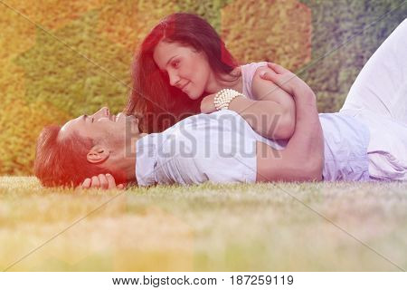 Loving young couple lying together in park
