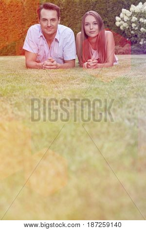 Portrait of young couple lying side by side on grass in park