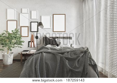 Messy modern bedroom with an unmade bed and a series of blank picture frames on the wall lit by daylight from a large window with curtains in a 3d rendering