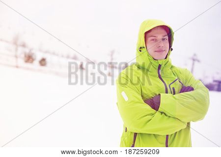 Portrait of young man in hooded jacket standing arms crossed in snow