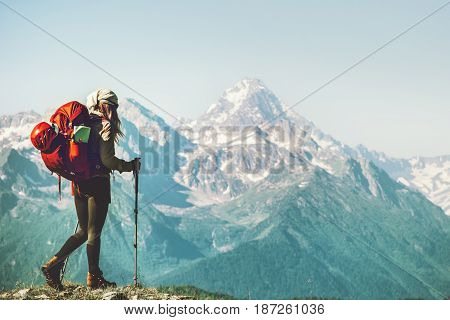 Traveler woman climbing to mountain summit with backpack Travel Lifestyle concept adventure summer vacations outdoor wild landscape on background