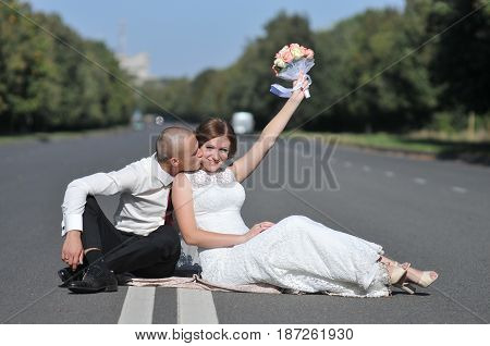 Young bride and groom posing for the camera outdoors in the street