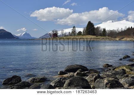 Seashore with clear blue water and stones in foreground and mountains with snow in background against a blue sky picture from the North of Norway.