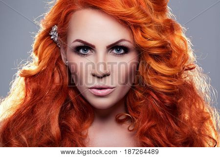 Portrait of beautiful red-haired woman in studio