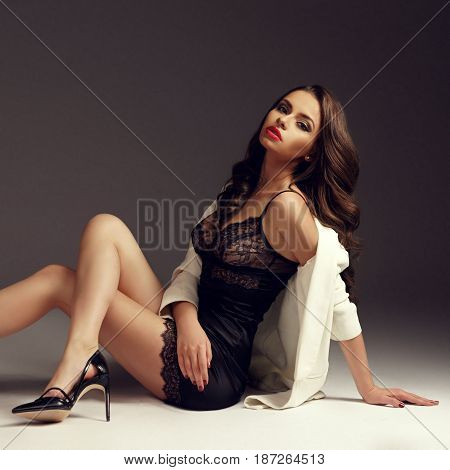 Young sexy girl in black nightie, high heels and white coat sitting on floor. Fashion style vogue portrait of brunette woman with long curly hair.