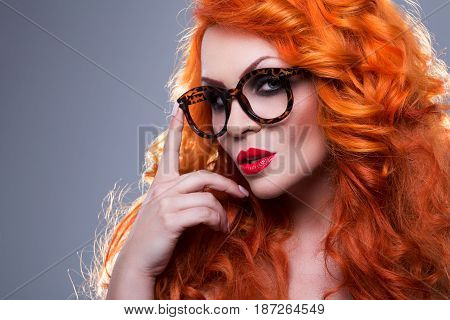 Portrait of a beautiful red-haired woman in glasses