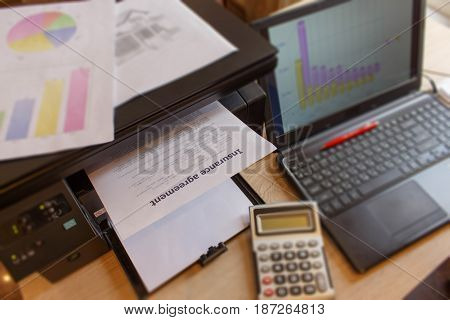 Insurance form with Laptop Printer pen dollars calculator on the table. Insurance concept. Homeowner insurance policy