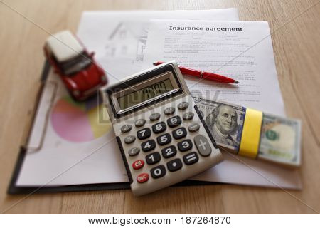 Close up view of the homeowner and car insurance policy. Insurance concept. Insurance form with pen notebook dollars calculator on the table