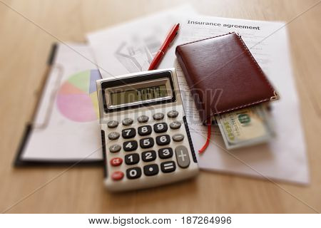 Close up view of the homeowner insurance policy. Insurance form with pen notebook dollars calculator on the table
