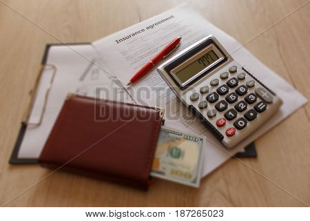 Close up view of the homeowner insurance policy. Insurance concept. Insurance form with pen notebook dollars calculator on the table