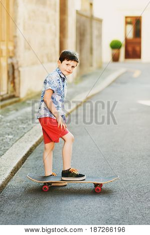 Funny stylish kid boy posing with skateboard outdoors, wearing blue print shirt and red shorts