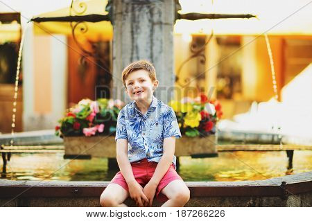 Outdoor summer portrait of adorable kid boy resting outdoors next to fountain on a very hot sunny day, wearing blue print shirt and red shorts