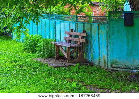 On the street near a metal zabo of blue color on a concrete podium self-made, roughly collected, wooden bench for rest is established.