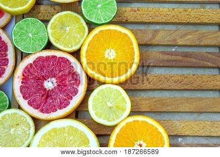 Fresh choped slices of different types of citrus on the wooden table