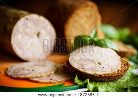 A sandwich with homemade sausage and rye bread on a wooden table