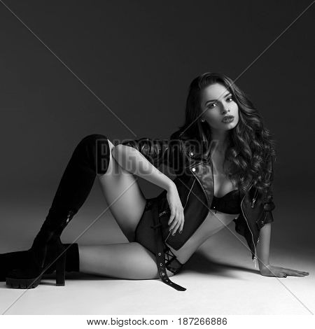 Fashion vogue style studio portrait. Young sexy girl in black lingeire, leather jacket and hessian boots sitting on white floor, posing and looking at you.