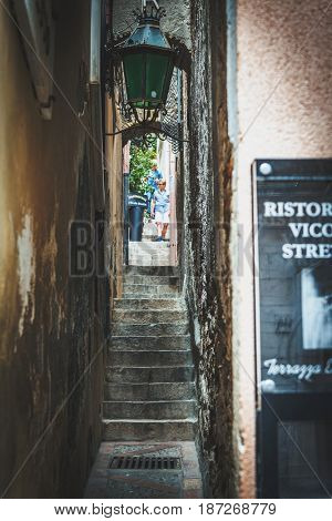 TAORMINA, SICILY, ITALY - Circa April, 2017: Narrow steep steps up the hillside between buildings in Taormina, Sicily Italy with a person right at the top descending towards the camera