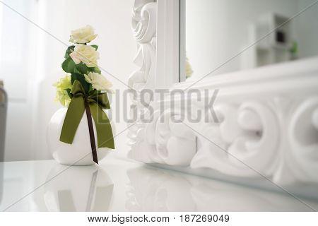 Elegant white jar of yellow roses with white furnishings.