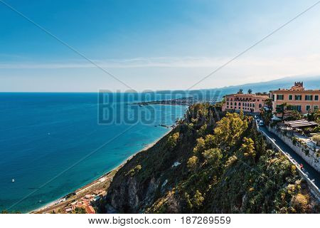 View of Taormina, Sicily, Italy perched on a hill overlooking the Bay of Giardini Naxos in the Ionian Sea, a popular tourist destination and resort