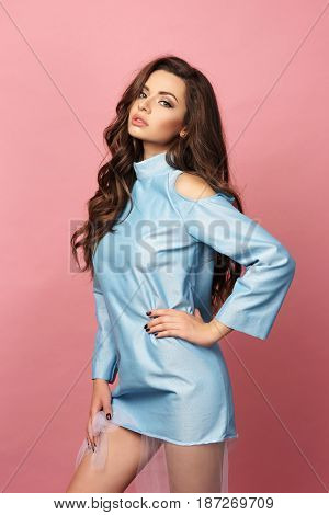 Pretty stylish girl with long curly hair wearing classy beautiful blue dress and posing against pink background. Fashion vogue style portrait of young beautiful woman