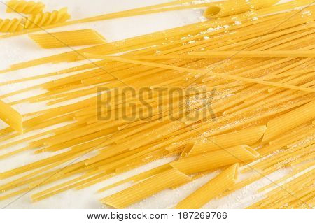 A closeup of spaghetti and penne pasta with traces of flour, shot from above on a white marble texture