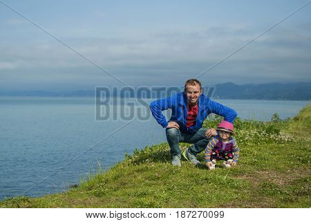 Dad and daughter are amusing and funny sitting on the edge of the beach by the sea