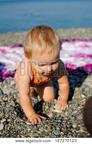 A little girl of one year crawls on pebbles on the beach by the sea