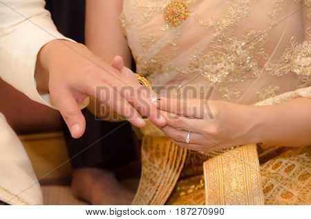 Marry me today and everyday hands of a wedding heterosexual couple. Groom put a ring on finger of his lovely wife.