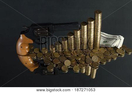 arrangement of coins and gun on grey background