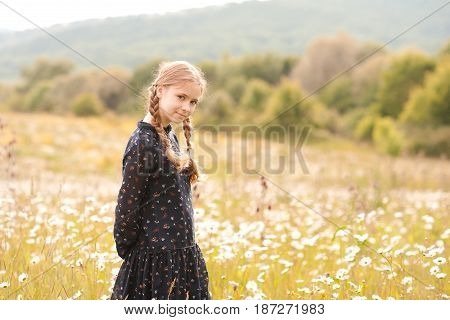 Blonde teen girl 14-16 year old posing outdoors. Looking at camera. Childhood.