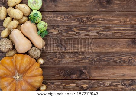 Autumn harvest on wooden table background. Pumpkin, zucchini, potatoes, onions and other vegetables