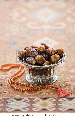 Subha- an islamic prayer beads along with bowl of sweet date fruits. Date fruits are considered scared fruit during holy month of Ramadan.