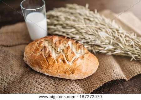 Bread, wheat and glass of milk, burlap background