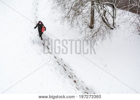 Woman with red bag going through the snow