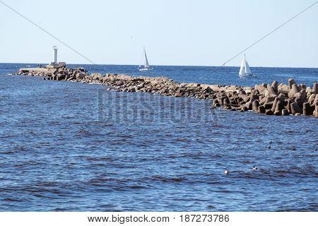 baltic sea pier breakwater and sailing yachts
