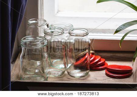 empty different jam jars on a windowsill
