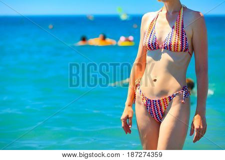 Slim woman with beautiful body in bikini posing on a beach