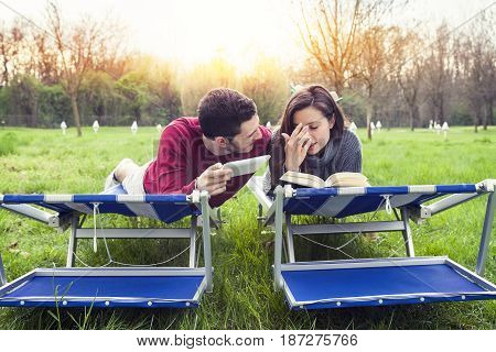 Nice Couple Relax On Deckchair Reading Book And Tablet