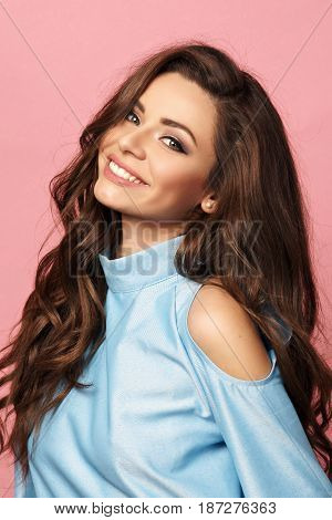 Pretty stylish girl with long curly hair wearing classy beautiful blue dress and posing against pink background. Fashion vogue style portrait of young happy smiling woman